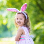 Girl with Easter bunny ears on an egg hunt
