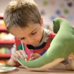 Boy painting ceramic dinosaur model